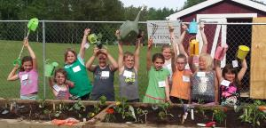 Healthy Sprouts participants holding gardening tools.