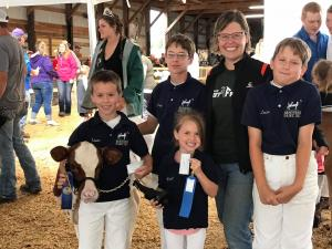 4-H volunteer with her children and dairy calf